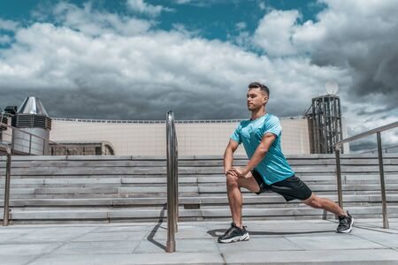 A male athlete does lunges summer city, stretching muscles before jogging, fitness training, sportswear, concentration and focus on goal. Stair background blue sky. Free space for text Stockfoto