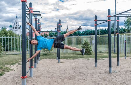 Young guy male sports athlete summer city sports ground abdominal muscle training, exercise flag, fitness training, workout healthy lifestyle. Sportswear, strength endurance, motivation. Happy smiles