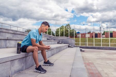 Athletic man, sitting steps, in hands phone, online training social networks, listening music in playlist. Rest after exercise. Free space summer city. Sportswear, shaker with protein water bottle