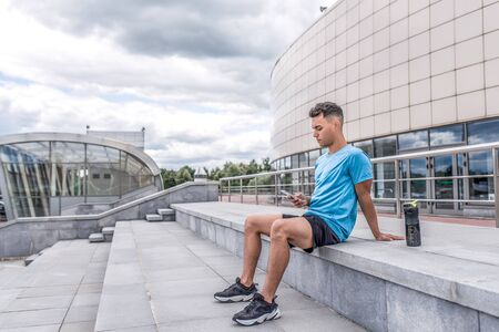 Athletic man summer city, sitting steps hands smartphone, online training social networks application Internet. Rest after exercise. Free space for text. Sportswear, shaker with protein water bottle