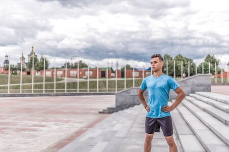 Young guy, male sports athlete, summer city, posing morning, free space for text, fitness training, workout healthy lifestyle. Sportswear, strength endurance, motivation, confidence, power thought