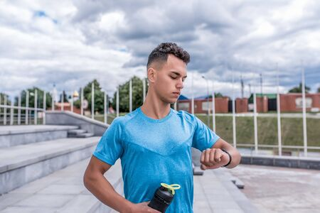 Young guy, sports athlete, summer city, looks clock, checks pulse heartbeat, stopwatch time timer, bottle protein, gainer, shaker with water, sportswear. Fitness training, workout healthy lifestyle