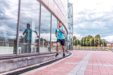 young guy, sports athlete, summer city, runs for jogging morning, free space, building windows. Fitness training, workout healthy lifestyle. Sportswear, strength endurance in jumping movement