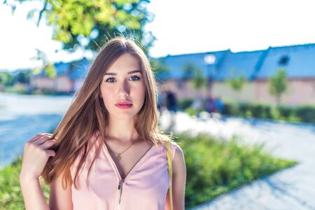Closeup portrait of girl in dress, in summer city, long hair, brunette, resting in nature, background trees, blue sky, interesting look, painted lips with lipstick