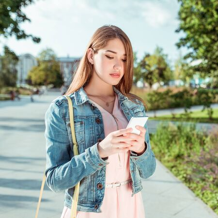 Beautiful student girl in jeans, in summer in city, stands in her hand phone, reads chat smartphone, application, online social networks, looks thoughtfully, writes message to Internet messenger