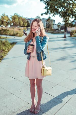beautiful girl in dress and jeans, in summer in city, stands her hand phone, rings smartphone, application, online social networks, happy laughs, smiles, joyful cheerful, coffee tea in cup
