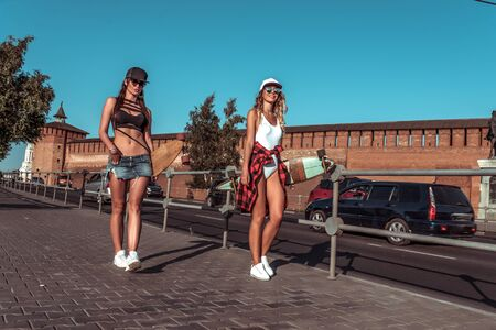 Two beautiful girls girlfriends summer city, go near road, background cars, longboard skate boards. Long hair tanned figure, sunglasses. Concept walk best sisters girlfriends. Happy smiling have rest