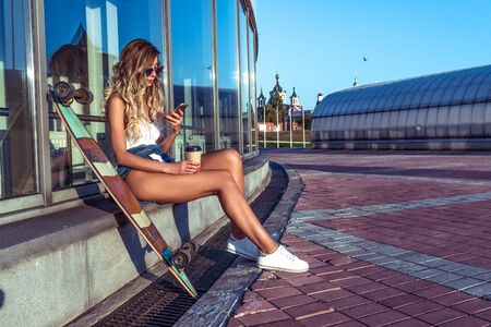 girl in summer city, longboard skateboard, sits on phone, reads message smartphone, online on Internet, writes on social networks, wi-fi online, long hair, sunglasses, cup coffee, free space text