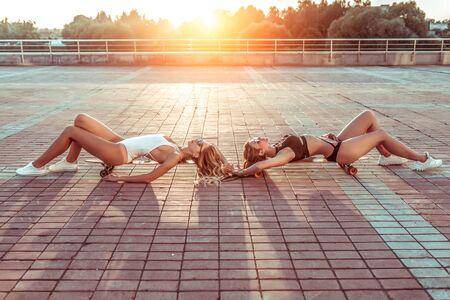Two beautiful girls girlfriends summer city, sunbathe skateboard background tiles longboard skate boards. In swimsuits sunglasses. Rest best sisters girlfriends. Free space, fashionable stylish women