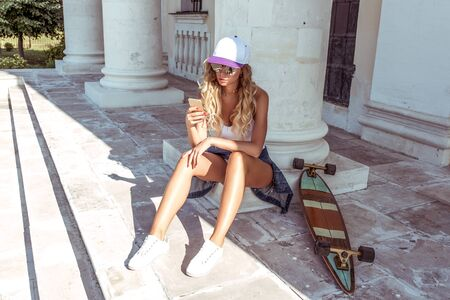 Girl in summer city, longboard skateboard, sits, holds phone hand, reads chat, message in Internet application, online social networks. Background building columns, long hair, baseball cap sunglasses