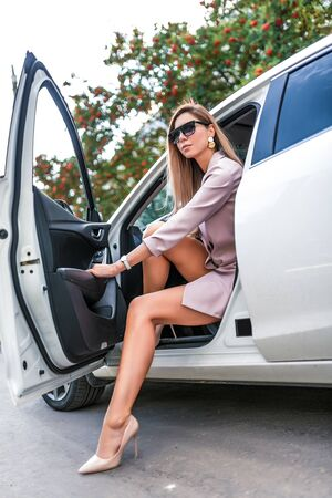 A beautiful woman in the summer in the city, getting out of the car, a white business class sedan, parking in the city, a business woman, long legs tanned figure, sunglasses, high-heeled shoes