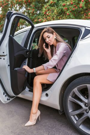 Business lady talking on phone, summer city taxi, getting out car, door opens, serious meeting an important call, business sedan in city taxi. Long hair formal suit, tanned figure, high heel shoes.
