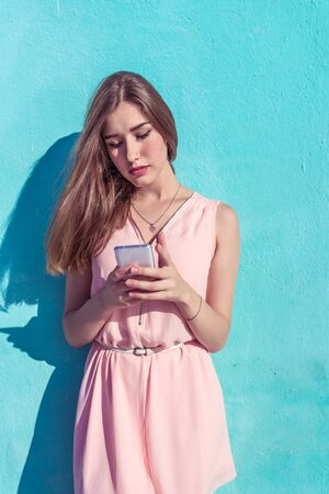 Girl student in a pink dress on a background of a turquoise wall, Summer in city. In hand of phone, correspondence in online application social networks, reads a message on a smartphone