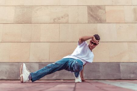 dancer in the summer in city, dancing break dance, bottom style, street dancers lifestyle, jeans t-shirt sneakers, sunglasses, active movement, background wall tile