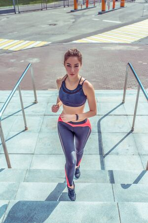 Female athlete runs on a jog in morning, in summer in the city, on the stairs, a beautiful girl doing fitness, youth lifestyle, healthy lifestyle in the city. Sportswear. Leggings. Top. Sneakers. Zdjęcie Seryjne