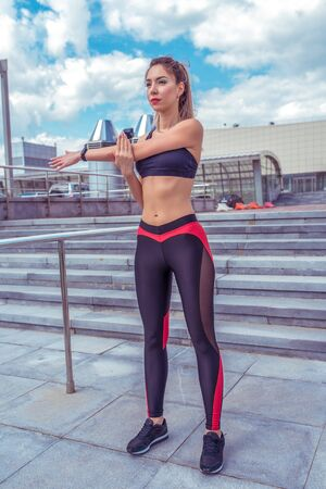 Athletic girl in the summer in the city, does a warm-up of the arms and shoulder, before fitness workout and in the morning. Sportswear. Leggings. Top. Sneakers. Cloud stair background Banque d'images