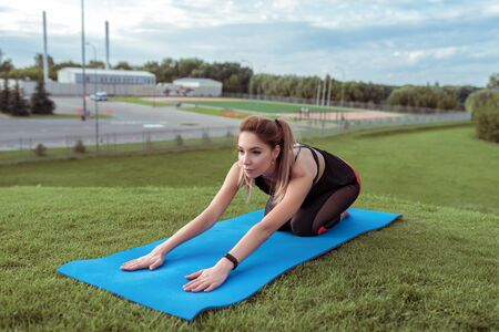 young and beautiful athletic girl, woman fitness stretching exercise, back muscles workout yoga mat, relaxes, concentration, summer park, background grass fitness, youth healthy lifestyle in city