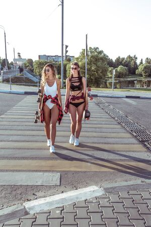 Two girlfriends walk in summer in city, background cross the road, swimsuits, shorts and baseball caps, skateboard long sunglasses. Weekend walk, youth lifestyle, modern style