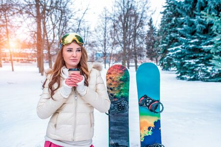 Girl in winter against snow of snowdrifts and trees, a cup of hot coffee of tea is warmed up, background of a board for snowboards, winter resort on weekend on vacation