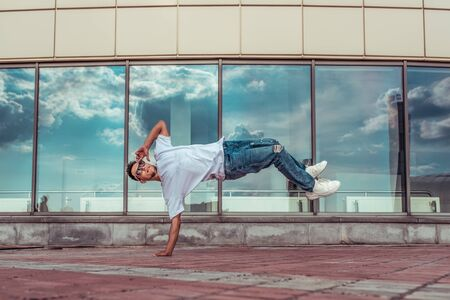Young stylish man window cloud background, flying air on one hand, guy dancer, summer city, dancing break dance, healthy fitness athlete life style, white T-shirt, jeans. Dancing to music