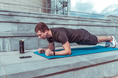 Male athlete, stands in bar, training muscles of back and abs, lifestyle fitness style will rob motivation. In summer in city. Shaker with water and protein, a timer application on a smartphone