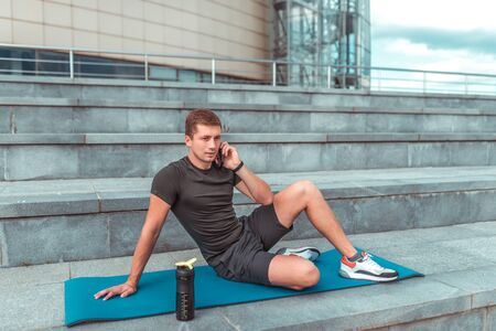 A male athlete calling on phone, resting after a workout, fitness lifestyle style will break out motivation. In the summer in the city. Shaker with water and protein, talking on a smartphone.