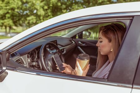 girl driving car, stands in parking lot, summer waiting for friends and girlfriends, reads message on her smartphone, holds cup of tea her hands with coffee. Summer city background trees Stock Photo