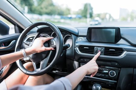 Close-up, female hand includes an emergency stop button, turning on dimensions, accident on road. The interior of car in summer in city, an alarm and accidents on highway Stockfoto