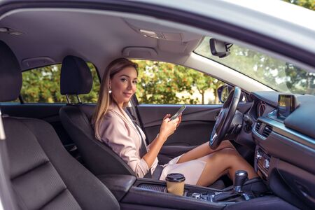 Business girl summer city car, happy smiling, meets passenger, business taxi, car rental, invitation travel, friendly driver, car interior, beautiful woman smartphone, message Internet phone map