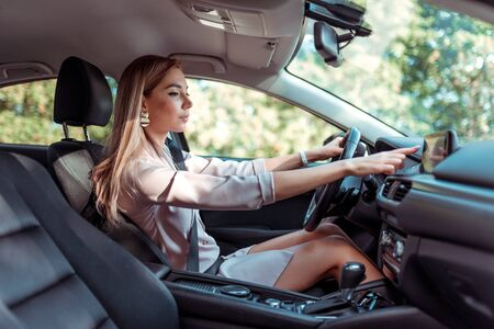 Business girl in summer city, sitting in car, hand selects mode on touch screen display, route selection, enabling functions, automatic transmission, pink suit, traffic jam in background trees