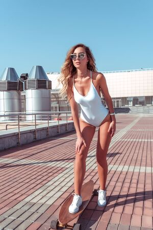 Beautiful girl in a white swimsuit, skates in the city in summer, skateboard, longboard, white sneakers sunglasses, youth lifestyle healthy lifestyle hipster fashion. Background tile. Фото со стока