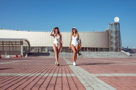 Two girls girlfriends are walking in city in summer, sunbathing in swimsuits, holding longboard skateboard, youth lifestyle healthy hipster fashion. The modern style of women Фото со стока