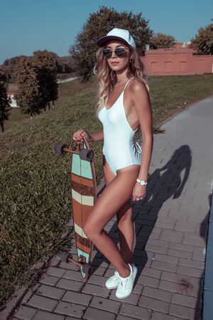 Beautiful girl in white bathing suit, summer city, skateboard, longboard, white sneakers sunglasses, youth lifestyle healthy hipster fashion. Baseball cap long hair tanned and athletic figure