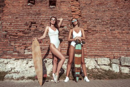 Two girls girlfriends are sunbathing brick wall, summer city, sunglasses swimsuits, skateboard, longboard, youth lifestyle, healthy hipster fashion. The modern style women. Free space text