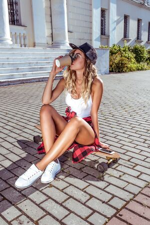 beautiful woman in summer in city sits on skateboard, drinks a hot coffee drink tea from cup. Skateboard, relaxation after sport fitness, workout. Tanned figure with long hair.