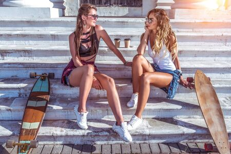 Two beautiful girlfriends talking in summer in city sitting on steps of college. Skateboard, relaxation after sport fitness, workout. Tanned figure with long hair. Cup coffee tea, longboard board