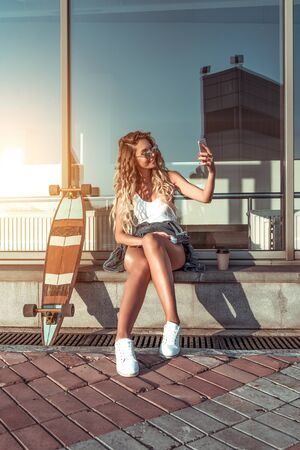 woman photographs herself on phone, takes selfie smartphone, sits city summer window, smiles happy, video recording online Internet call. Skateboard, relaxation after sport fitness, workout Фото со стока