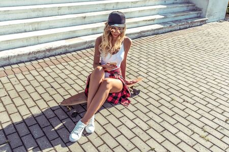 beautiful woman in summer in city sits, reads a message in a smartphone, watches video in phone application. Skateboard, relaxation after sport fitness, workout. Tanned figure with long hair