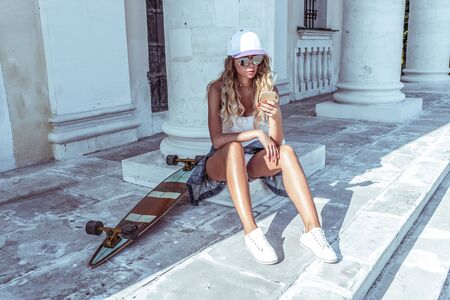 beautiful woman in the summer in the city sits on a mobile phone, reads a message, on social networks. Skateboard, relaxation after sport fitness, workout. Tanned figure with long hair Фото со стока