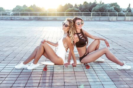 Two happy girlfriends girls sit skateboard, rejoice have fun, play, summer city. Holiday vacation on weekends, entertainment of modern teenagers of fashionable hipsters. Sunbathe tanned slim figures Фото со стока