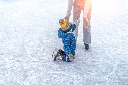 Mom with baby boy 3-5 years old, learn train, ride winter city rink, ice skating. The child gets up, fell on skates, kneels, play fun rest on weekend first steps child skates. Free space for text
