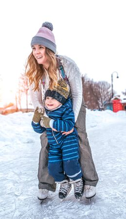 Sister with little nephew, boy 3-5 years old, winter city ice rink, happy ones ride, have fun playing studying weekend nature. Education training ice skating. Winter snow drifts, warm clothes, hats