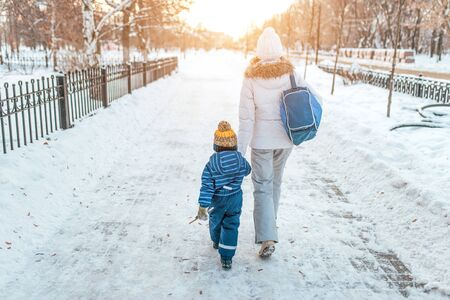 Woman mother walks down street winter, with small child, boy or girl 3-5 years old, view from rear, background road snowdrifts, returns kindergarten school workout. Holiday weekend warm clothes