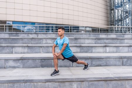 A male athlete makes lunges, training legs, in summer in city, in morning in fresh air. Youth lifestyle, active modern guy athlete, free space for text motivation. Stock Photo