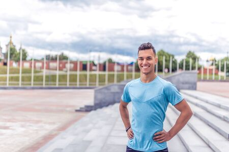 Handsome muscular athlete man smiles, looks carefully, close-up happy rejoices coach, summer city, sports shirt motivation youth lifestyle, outdoor training. Motivation active. Free space for text.