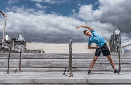 A male athlete in the summer in city does stretching, preparing for jogging, training in the morning in the fresh air. Free space for motivation text. Youth lifestyle, active modern guy athlete.