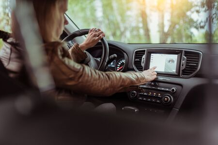 Woman girl in summer car interior in forest park, selects navigation touch screen, satellite internet application. Lost in search of a route, parking in fresh air rest in forest. Фото со стока
