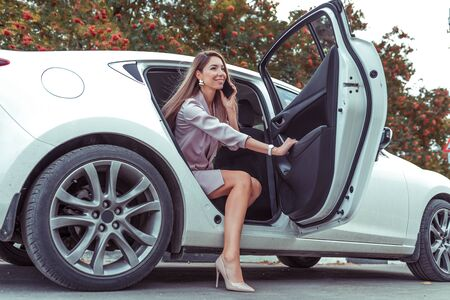 Happy beautiful woman calling phone, getting out car business sedan VIP class taxi, summer spring autumn city. Pink suit high heel shoes. Emotions of joy happiness, good deal, emotional call