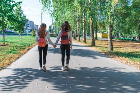 Teenage girls in sweaters, back view, walk with backpacks behind, summer autumn and spring in the city, weekend after school. Background trees grass, park. 版權商用圖片