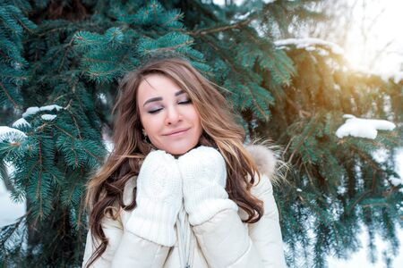 Beautiful girl warm white jacket, winter in snowy park, background spruce white snow, happy warms up warm knitted mittens, relaxes in winter resort weekend. Emotions pleasure and enjoyment